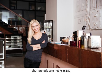 Young attractive female receptionist of beauty salon standing with hands crossed