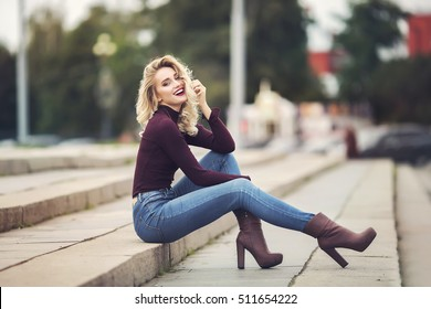 Young attractive female sitting on stone stairs