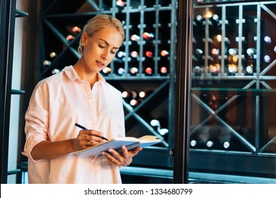 Young attractive female sommelier is writing inventory for red wine she have already tasted in stock in the shop. Multiethic woman is taking notes about wine to her notebook in the winery.