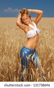 Young and attractive female standing in the wheat yard on a sunny day