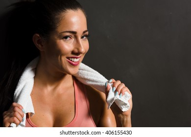 Young attractive female taking a break from gym workout.