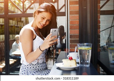 Young attractive female taking picture of her coffee shop breakfast with mobile phone camera, smiling gorgeous latin woman photographing cake with berries on her cell phone, people using technology