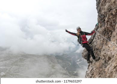 young attractive female university student on a vertical and exposed rock face climbs a Via Ferrata while smiling and waving and making a peace sign