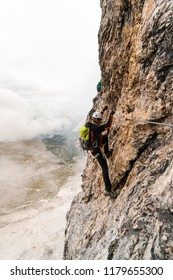 young attractive female university student on a vertical and exposed rock face climbs a Via Ferrata in Alta Badia in the South Tyrol