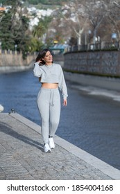 A young attractive female wearing gray a sweatshirt and sweatpants and walking near a river