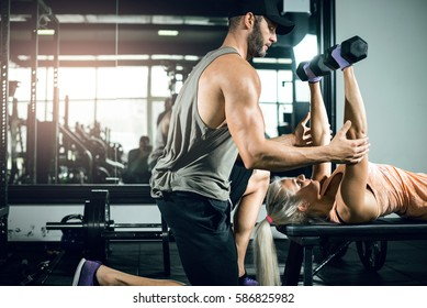 Young attractive fit blonde caucasian girl doing dumbbell chest press exercise with help of her personal trainer. Toned image.