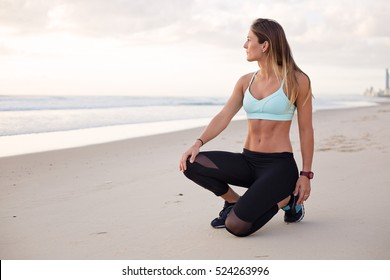 Young attractive fit and healthy woman looks out to the ocean with a look of inner peace and contentment from daily working out and looking after her body.