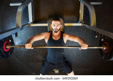 Young attractive fit Man with beard In Gym Exercising Chest On The Bench Press. Bodybuilding, motivation, active, healthy lifestyle. Top view
