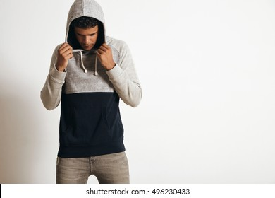 Young attractive and fit man in blank grey black hoodie sweater posing in front of white wall, looking down