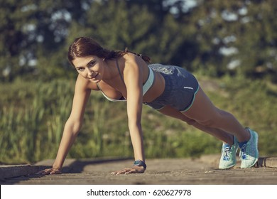 Young attractive fit woman in summer sportswear doing push ups or press ups exercise for upper body muscles, outdoors on a sunny day.