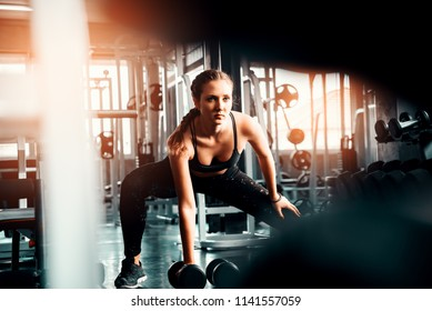 Young attractive fitness caucasian girl  lifting dumbbell weights in gym .Sporty woman showing her well trained body . Well developed muscles strong training .Workout training healthy concept.