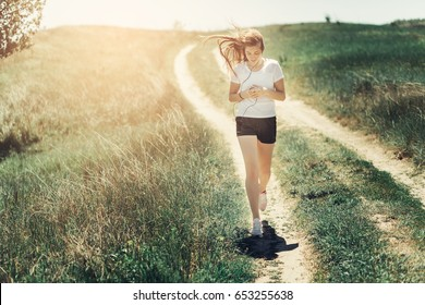 Young attractive fitness sport teen girl running at nature and listening music