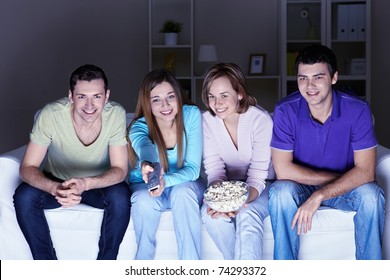 Young attractive friends watch TV at home