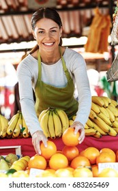 Young attractive fruit market saleswoman selecting fresh fruit on the street market.
