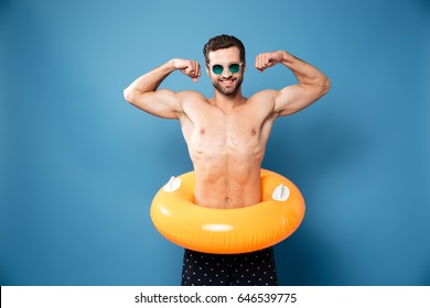 Young attractive funny man in swimming circle showing his biceps isolated over blue background