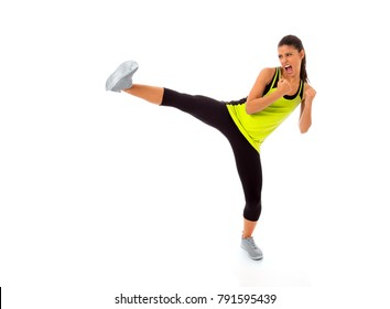 young attractive and furious hispanic sport woman in fight and kick boxing training workout throwing aggressive leg attack isolated on white background in gym exercise and personal defense concept