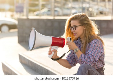 Young attractive girl activist with loudspeaker. She holds an advertising action on the city street