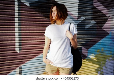 young attractive girl with a backpack wearing a white t-shirt standing on a graffiti wall background