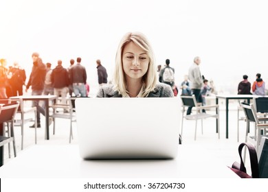 young attractive girl with blonde hair working with a laptop computer outside. Beautiful businesswoman searching information on the Internet