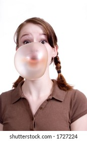 Young attractive girl blowing a giant bubble with chewing gum.