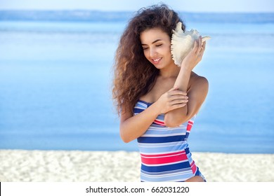 A young attractive girl in a colorful striped swimsuit holds a large, white shell on the beach by the sea.