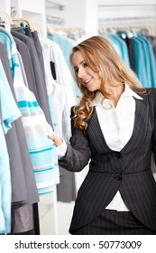 The young attractive girl considers clothes in shop
