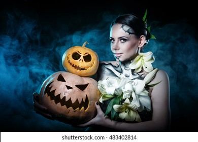 Young attractive girl with creative make-up for Halloween. Portrait close-up pumpkins. Mysterious and frightening image of lilies and red eyes. Smoke in the background. Jack-o'-lantern