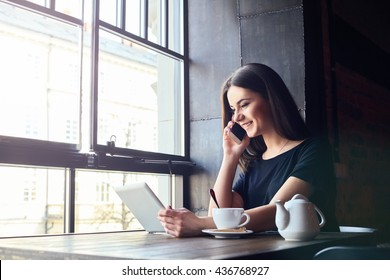 Young attractive girl with cute smile talking on mobile phone while sitting alone in coffee shop during free time and working on tablet computer. Happy female having rest in cafe. Lifestyle