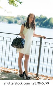 Young attractive girl dressed elegance close to river