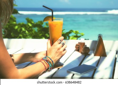 Young attractive girl drinking healthy juice on the beach.