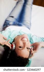 Young attractive girl enjoying music through headphones, lying on the sofa