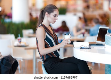Young attractive girl with glass of coffee in cafe. Lifestyle business portrait