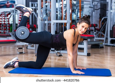 Young, attractive girl at the gym in sportswear while performing the glute kickback exercise with a five kg dumbbell for her gluteus and hamstring muscles.