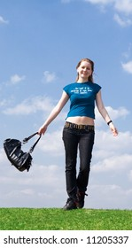 The young attractive girl with a handbag on a background of the blue sky
