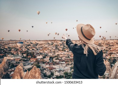 Young attractive girl in a hat stands on the mountain with flying air balloons on the background. Finger pointing girl on the sunrise. View from the back. Famous tourist Turkish region cappadocia