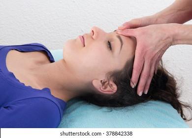 Young attractive girl having head massage at spa resort