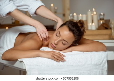 Young attractive girl having massage relaxing in spa salon.