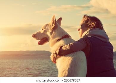 年轻有吸引力的女孩与她的宠物狗在海滩,彩色图像