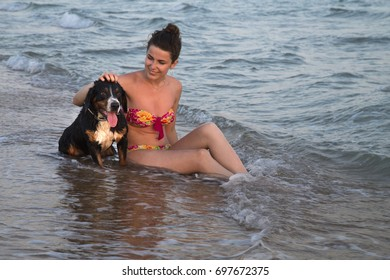 Young attractive girl with her pet dog sitting on the sand beach, in waves, during sunset.