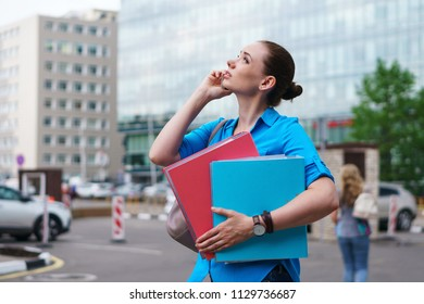 Young attractive girl is holding a cell phone and folders for papers. She is talking on the phone and looking up.