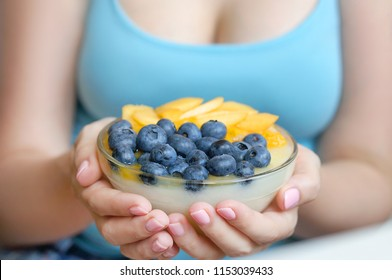 Young attractive girl holding healthy breakfast bowl. Pudding with fresh juicy fruits. Close up photo