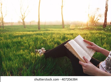 young attractive girl immersed in the world of dreams and fantasy reading a bestseller in the park sitting on the grass in the rays of the setting of the spring sun. girl peep over his shoulder.