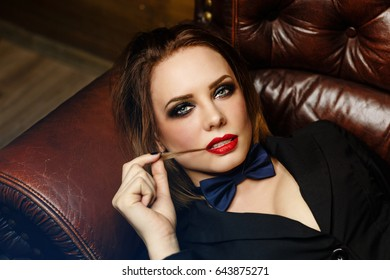 Young attractive girl in a jacket and bow tie. Femme fatale. Evening makeup smokey eye. She lies on a leather couch and coquettishly bites her hair.