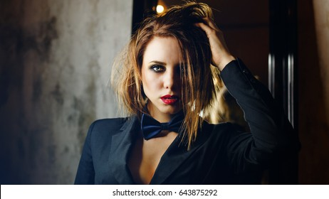 Young attractive girl in a jacket and bow tie. Femme fatale. Evening makeup smokey eye. She straightens her hair. Passion and desire