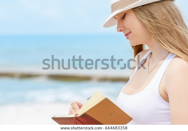 Young attractive girl with kind smile is writing some idea or letter in her note book by pen on background of blue sea at sunny summer day.