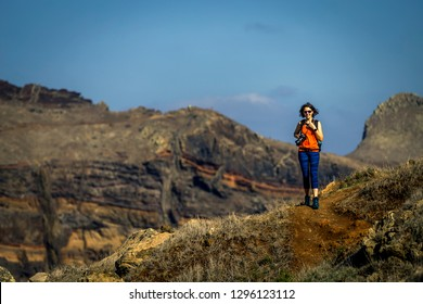 Young and attractive girl in orange shirt and blue leggings is hiking by the tourist's trail on Madeira island, Portugal. Sunny day.