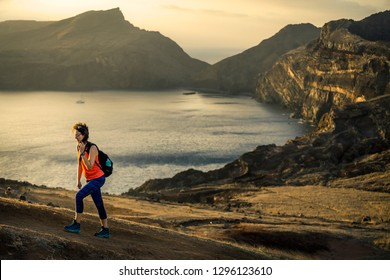Young and attractive girl in orange shirt and blue leggings is hiking by the tourist's trail on Madeira island, Portugal. Sunny day. The end of the trail, she is climbing up on sunset.