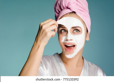 young attractive girl with a pink towel on her head removes a white nutritious mask from her face