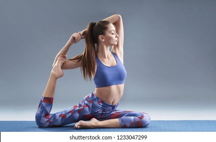 Young attractive girl practicing yoga. Solid background, copy space.