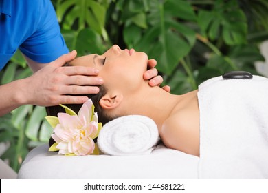 Young attractive girl receiving head massage at health spa center